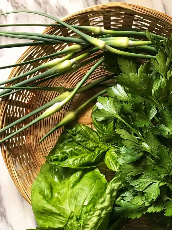 A wicker basket wit garlic scapes, fresh basil and parsley.