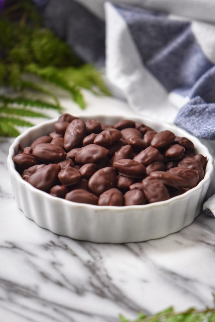 Chocolate covered almonds in a white bowl.