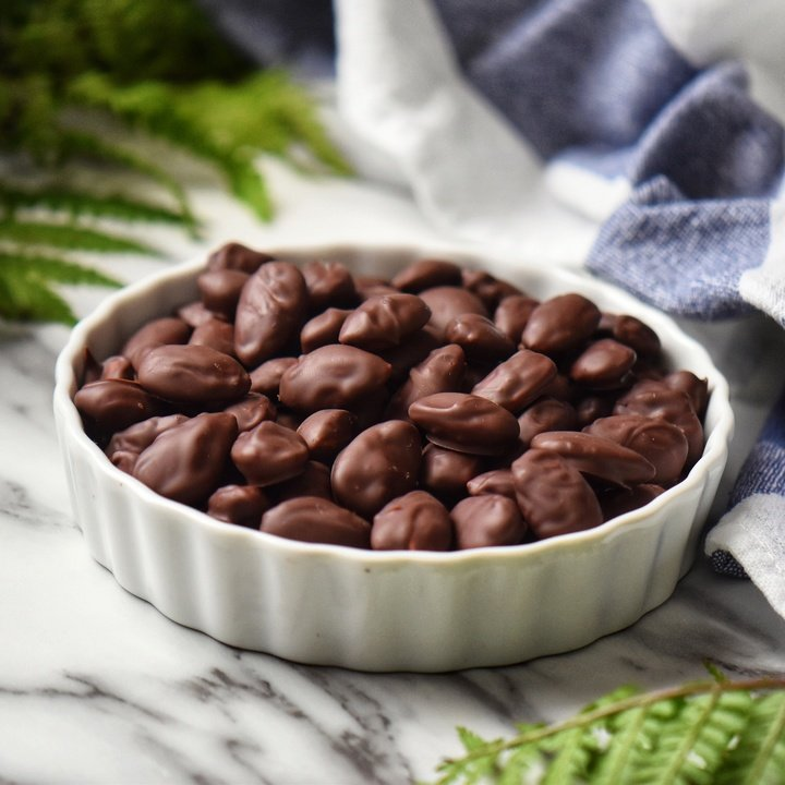 Chocolate coated almonds in a white ceramic bowl.