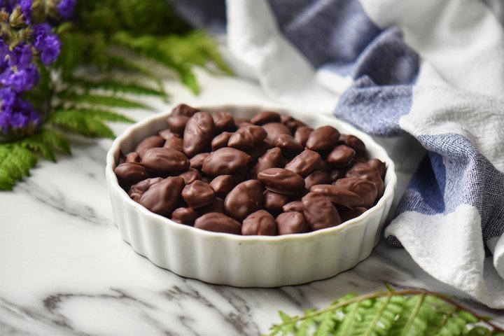 A white ceramic dish filled with dark chocolate almonds.
