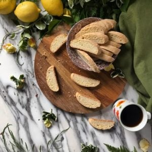 Biscotti scattered on a wooden board, surrounded by fresh lemons and a cup of coffee.