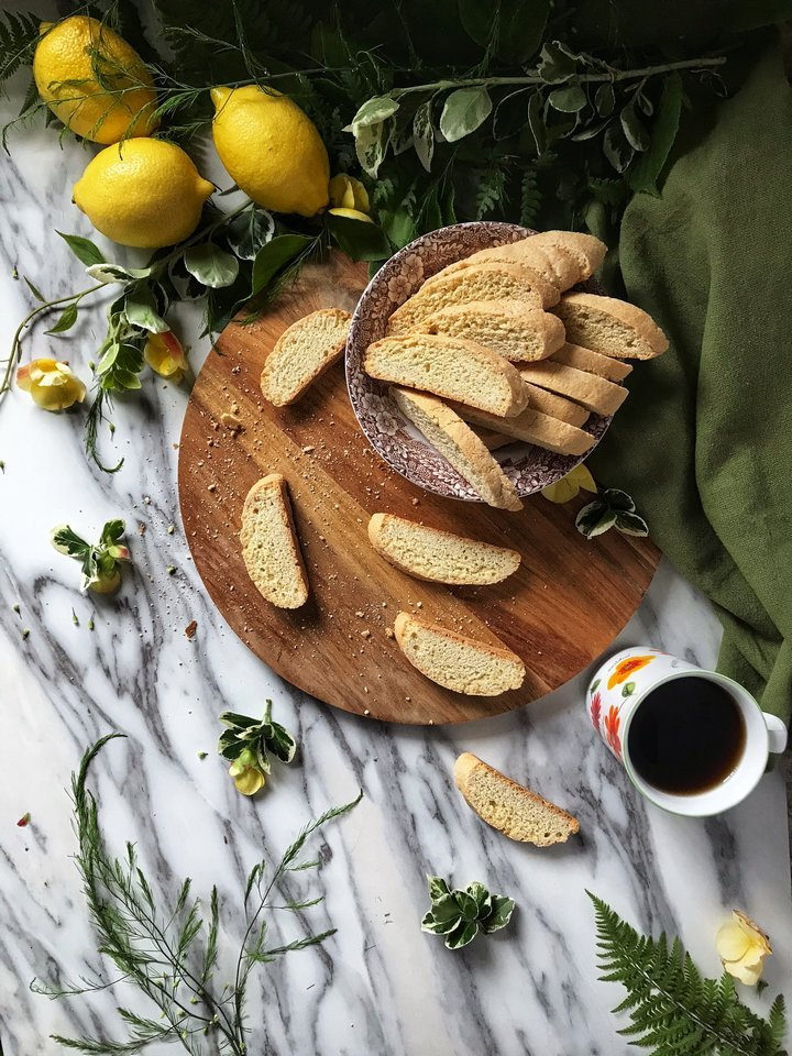 Sliced lemon biscotti surrounded by fresh lemons, green leaves and a cup of coffee.