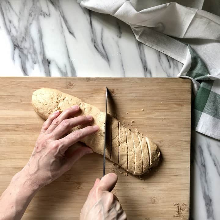 A serrated knife is used to slice the biscotti log.