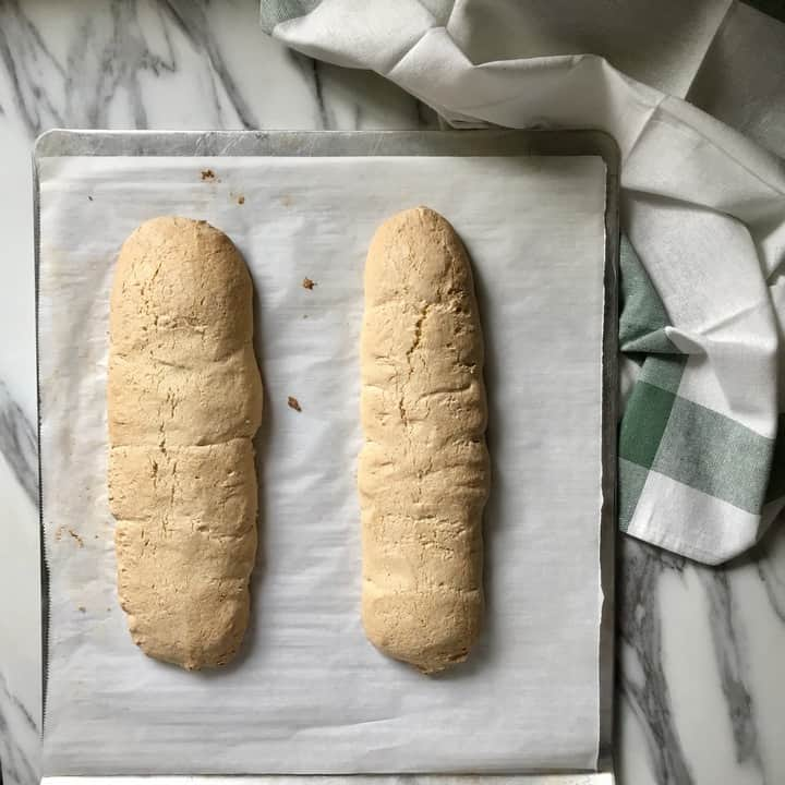 Two freshly baked biscotti loaves on a parchment lined baking sheet.