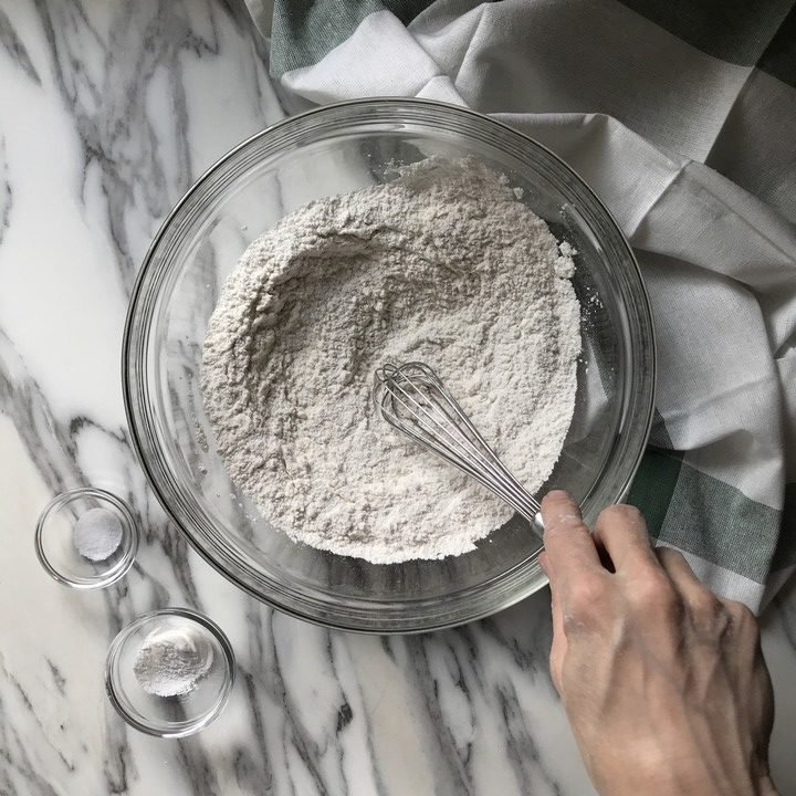 Baking powder and salt about to be sifted together with flour in a large bowl.