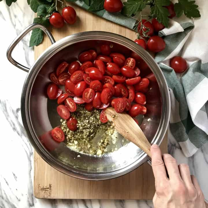 Chopped cherry tomatoes being combined with sauteed garlic and pesto sauce.