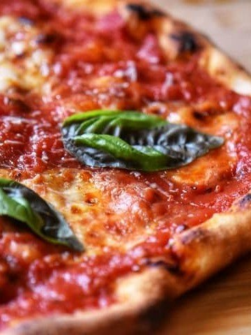 Basil leaves garnish a freshly grilled Italian pizza.