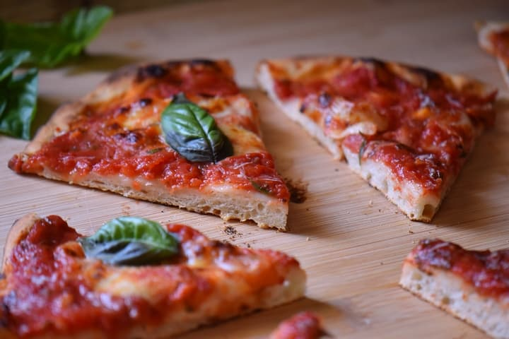 Slices of margherita Pizza on a wooden board.