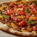 A potato pizza topped with grated cheese, chopped tomato and dill.