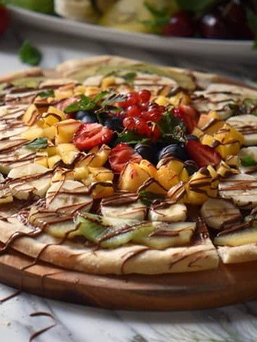 A pizza topped with fresh fruit on a wooden serving board.