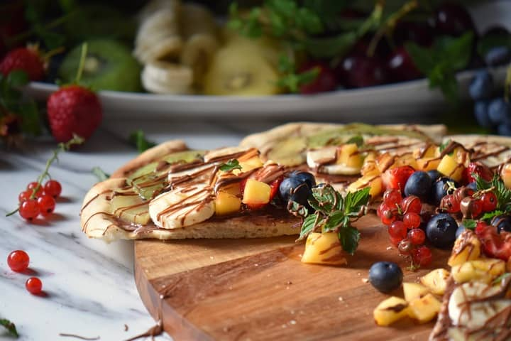 A fruit topped pizza on a wooden board.