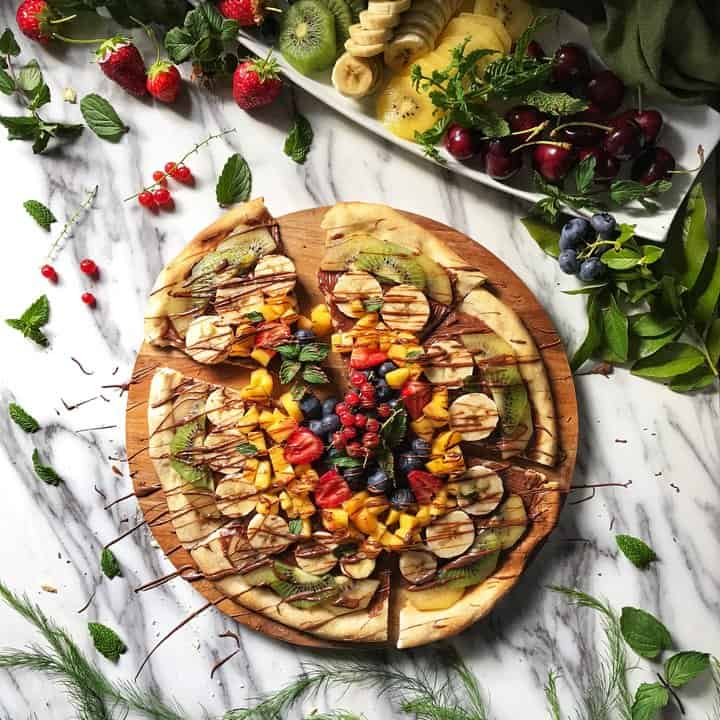 A pizza crust covered with a chocolate spread and topped with seasonal fruit.