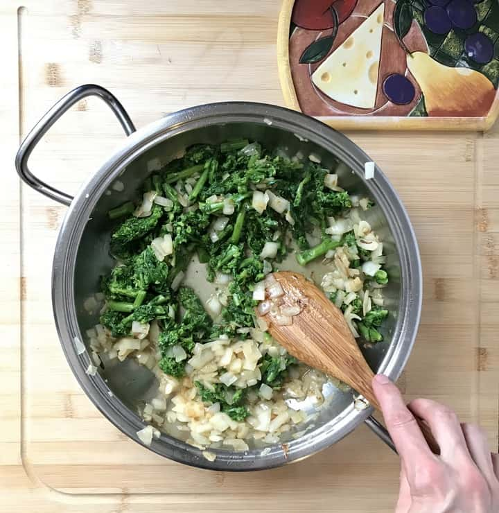 Parboiled Broccoli rabe added to sauteed onions and garlic in a pan.