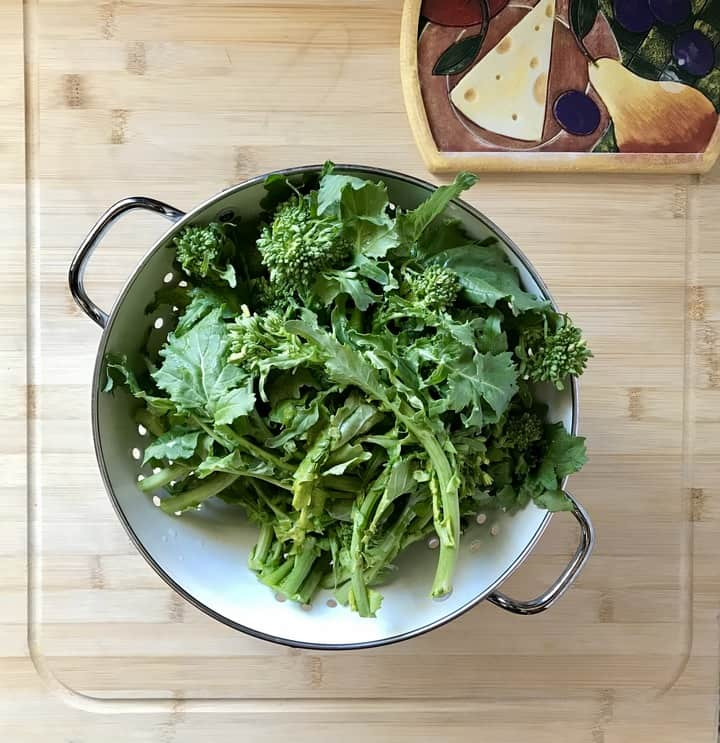 Broccoli rabe in a colander, about to be rinsed.