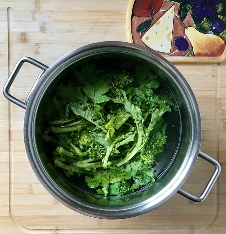 Broccoli rabe in a large pot of salted water, about to be parboiled.