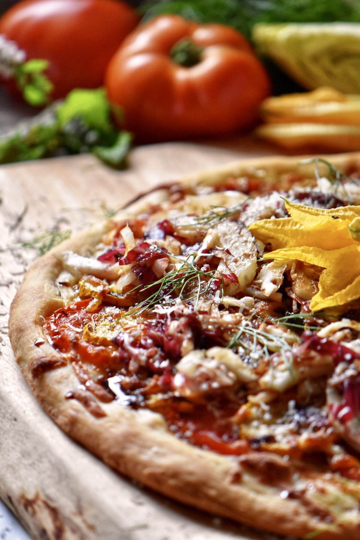 A pizza topped with endive, radicchio and fennel on a wooden board.