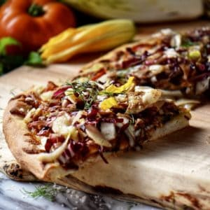 A slice of pizza, ready to be picked up and eaten, on a wooden board.