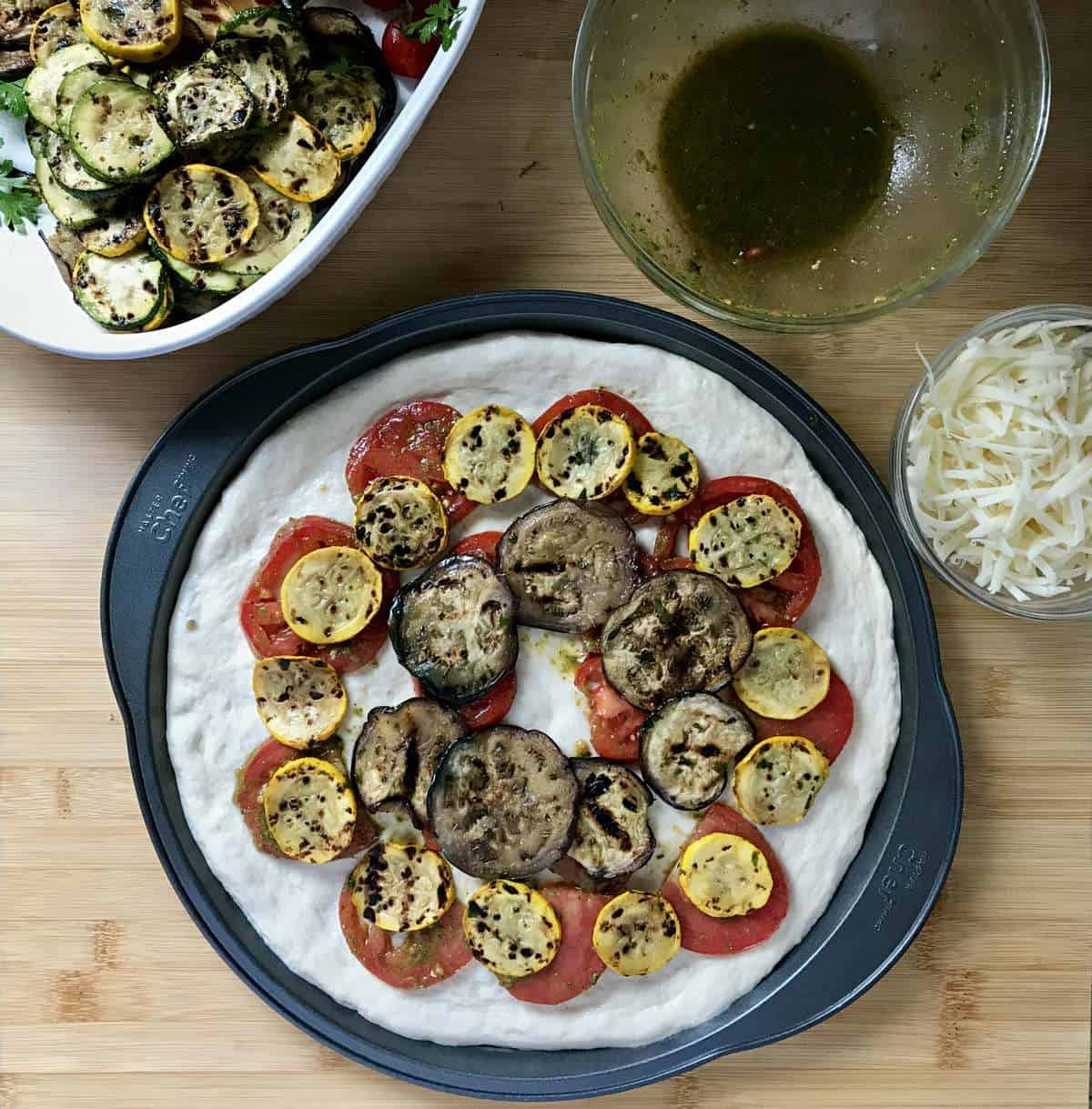 Grilled vegetables placed over the marinated tomatoes create the second layer of this vegetarian pizza.