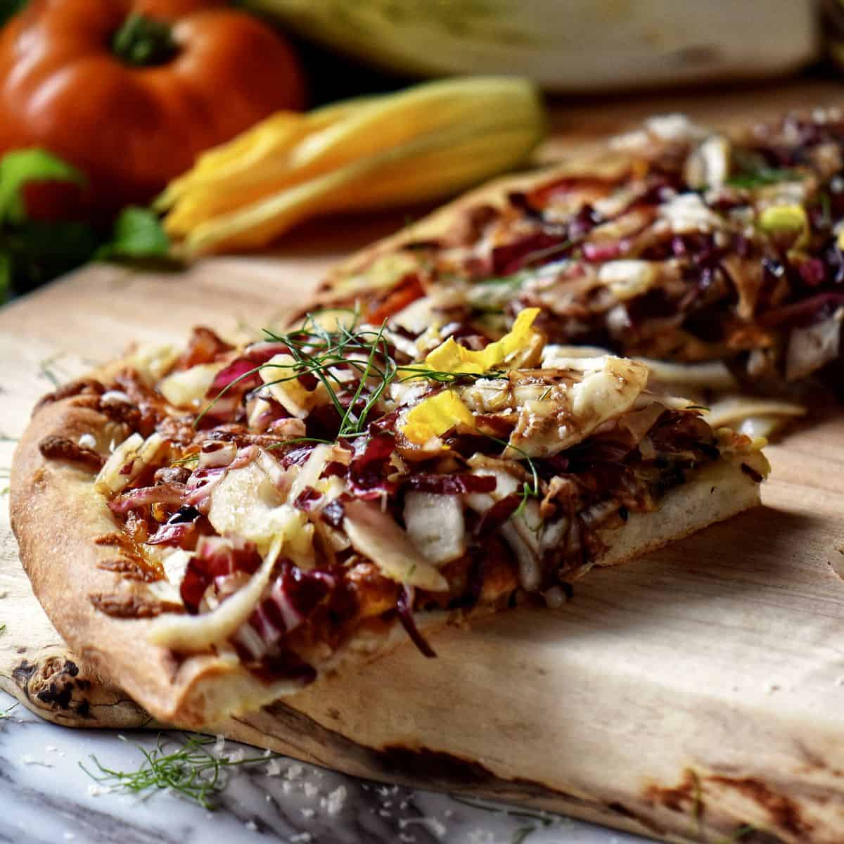 A piece of pizza topped with endive, radicchio and fennel, on a wooden board.