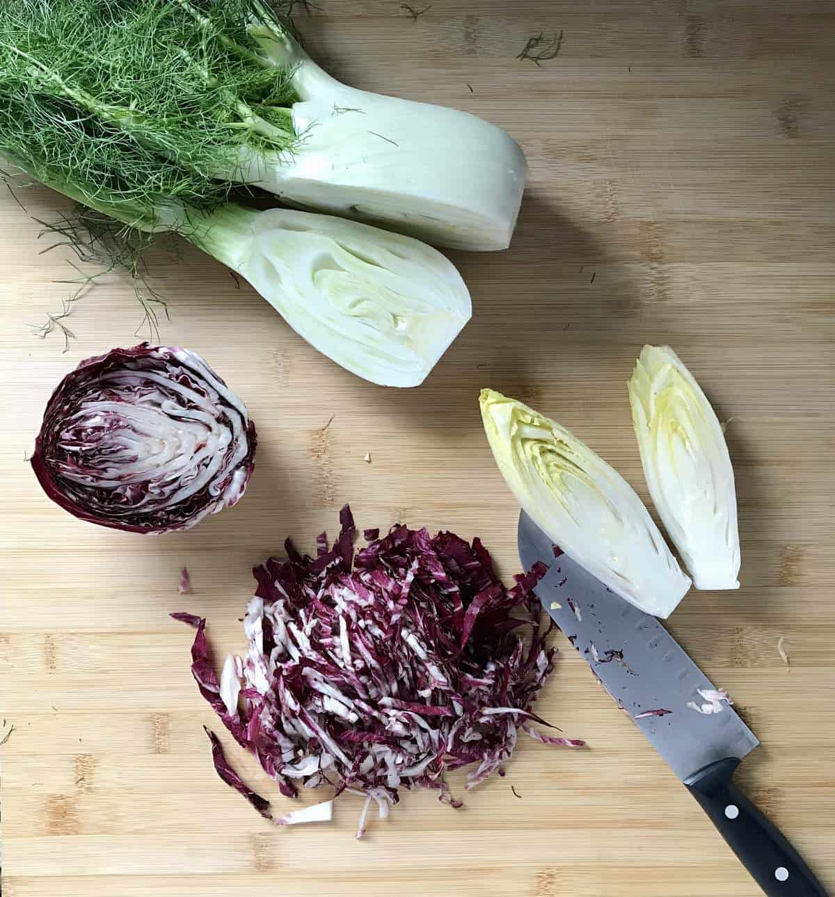 Chopped radicchio next to a head of fennel and endive on a wooden board.
