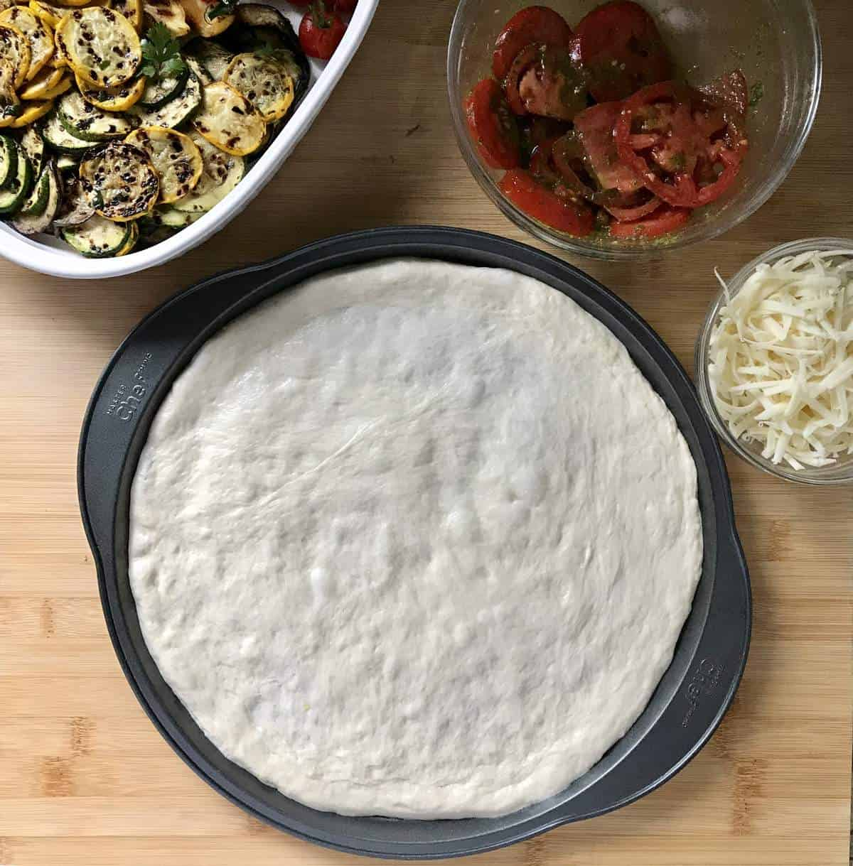 Stretched out pizza dough in a round pizza pan.