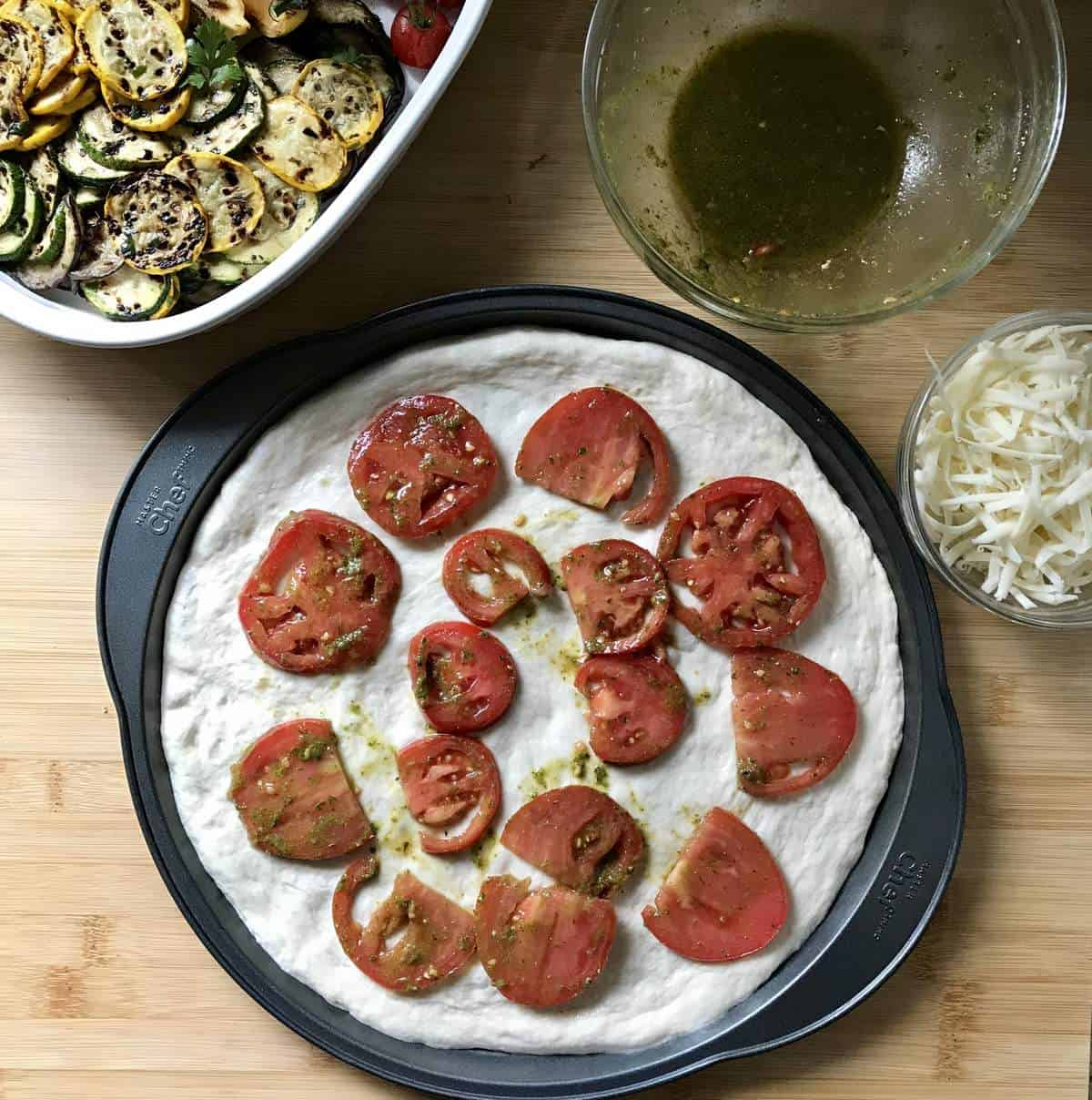 Marinated tomatoes (in basil pesto) on pizza dough creates the base of the salad pizza.