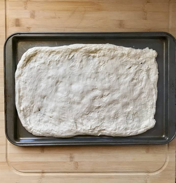 Pizza dough is stretched out on a baking sheet pan.