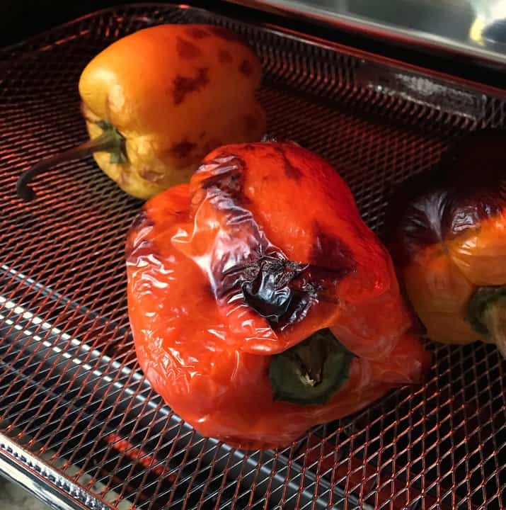 Bell peppers in an air fryer basket.