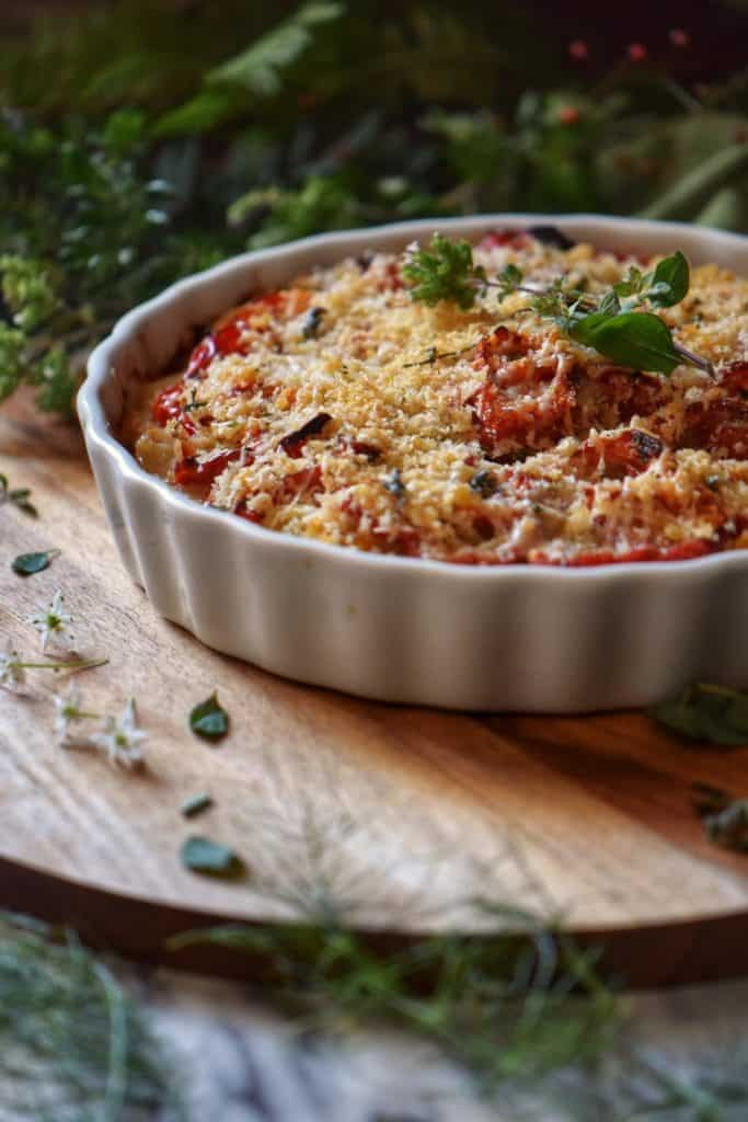 A tomato potato casserole in a white ceramic baking dish.