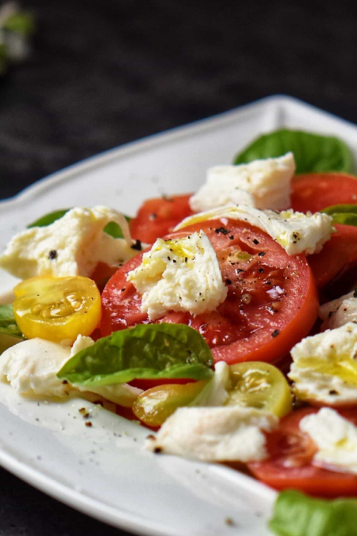 Fresh Mozzarella cheese, tomato slices and basil leaves on a white serving platter.