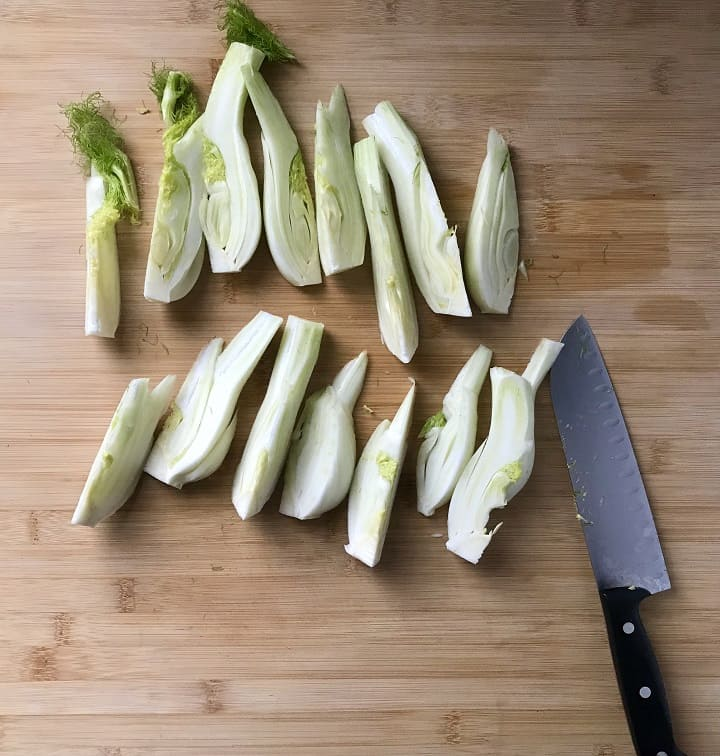 Fennel bulbs sliced in quarters, on a wooden board.
