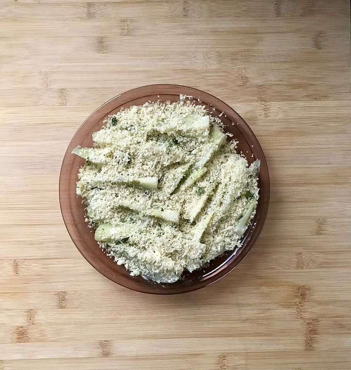 Sliced fennel topped with a mixture of panko bread crumbs and herbs in a round dish, ready to be oven baked.