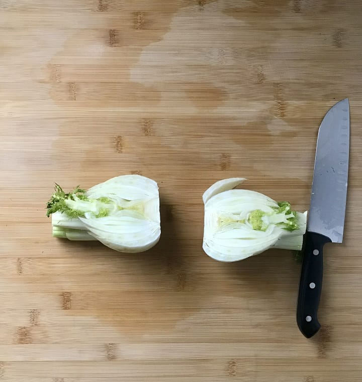 A fennel bulb, cut in half, on a wooden board.
