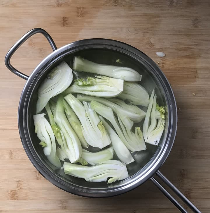 Sliced fennel simmering in a large pan of salt water.