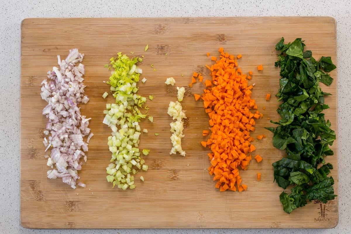The vegetables to make a soffritto on a wooden board.