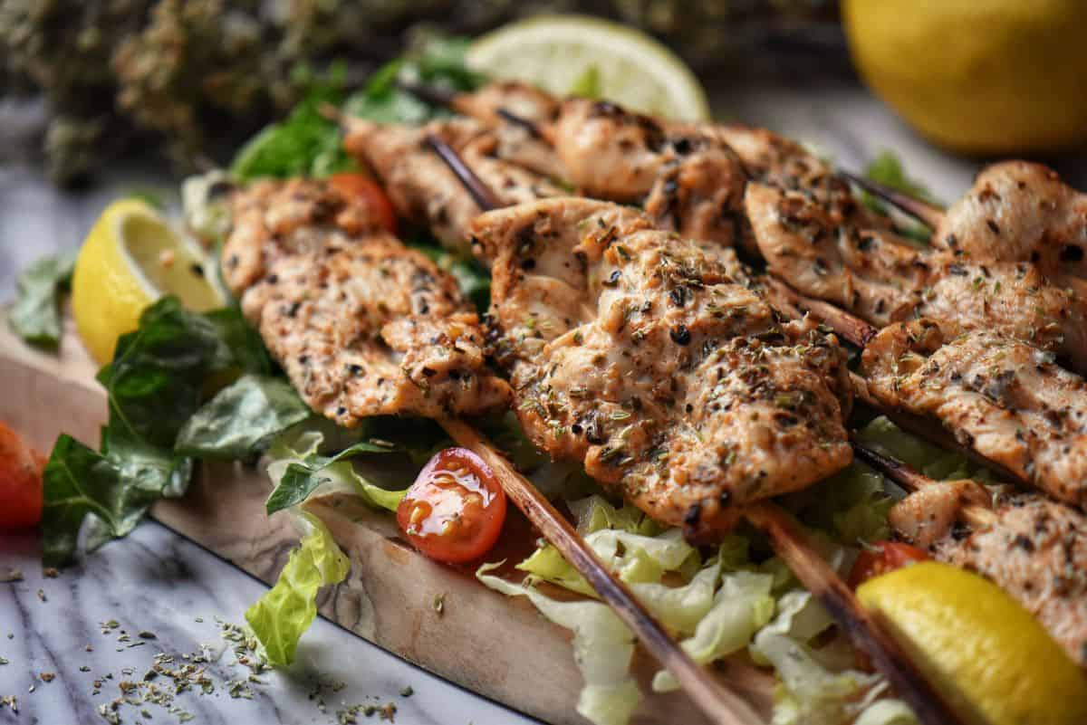 Skewers of grilled chicken on a wooden board.