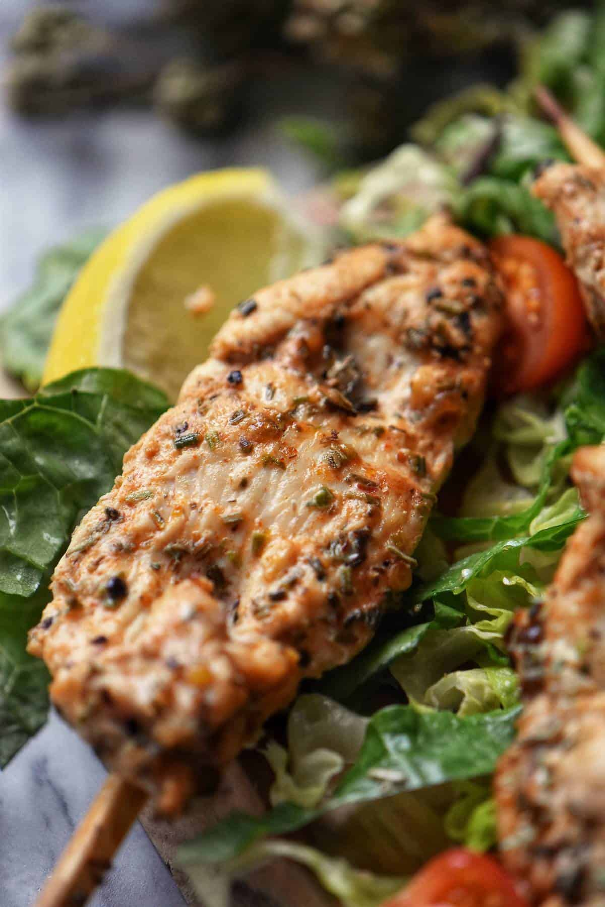A single chicken skewer on a bed of lettuce surrounded by lemon wedges.