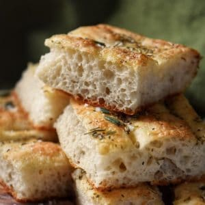 The soft texture and open crumb of focaccia bread is visible.