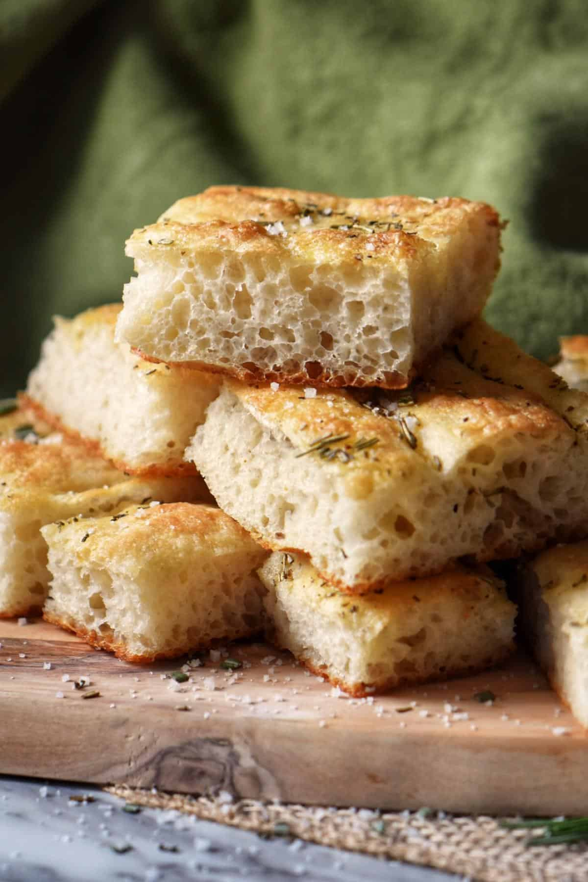 Slices of focaccia bread piled high on a wooden board.