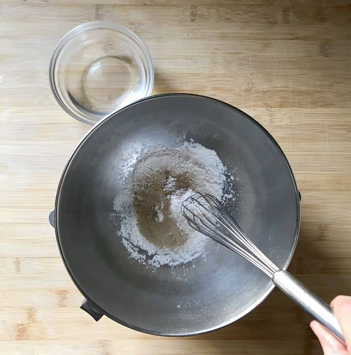 Dry active yeast and all purpose flour are being whisked on a bowl of a stand mixer.