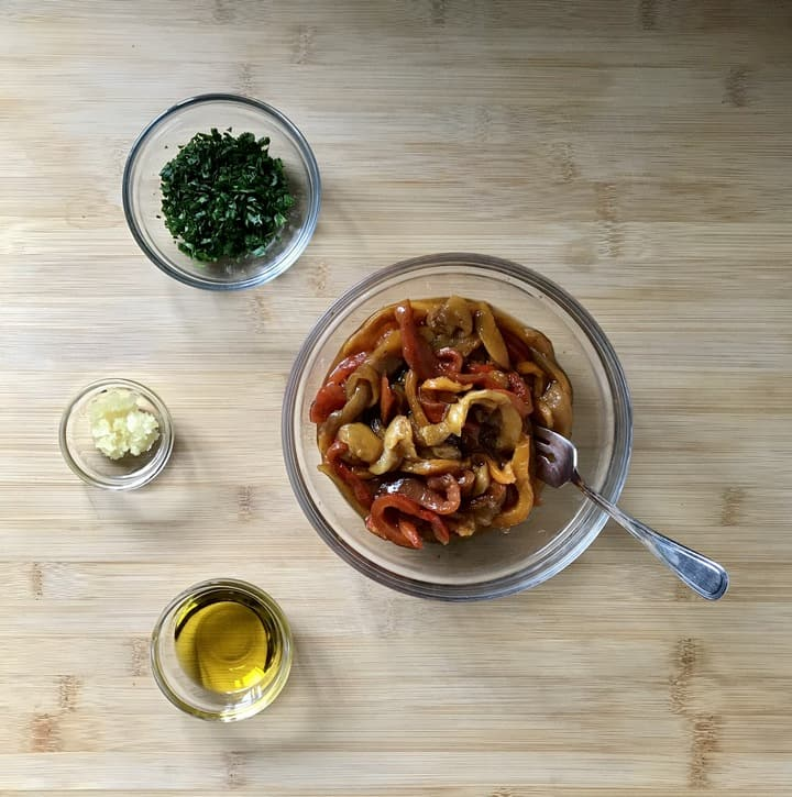 Olive oil, parsley, garlic and roasted peppers in individual bowls.