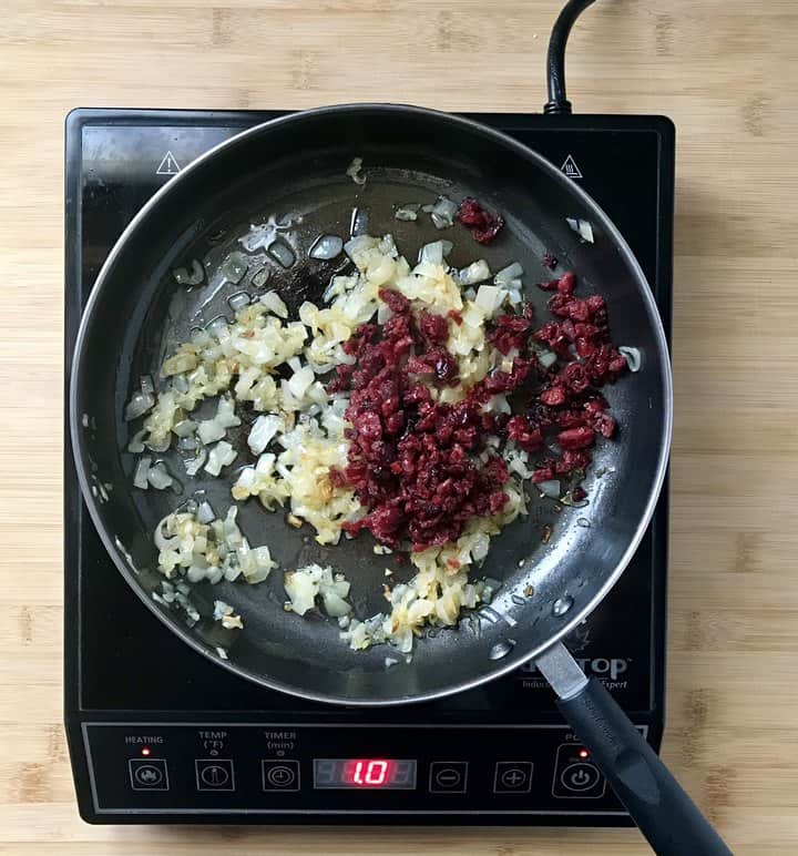 Chopped cranberries and sauteed shallots in a pan.