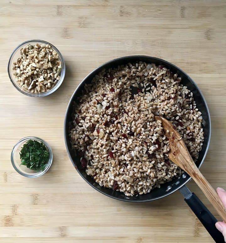 Chopped walnuts and parsley in bowls, next to a pan of warm farro.