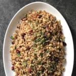 Warm farro salad garnished with chopped parsley in a white oval dish.
