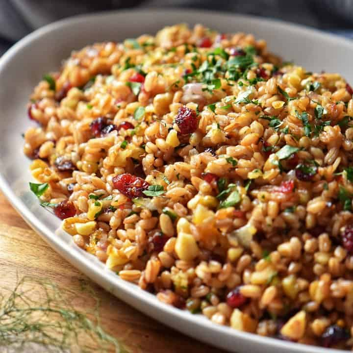 Warm farro salad, garnished with chopped parsley in a bowl.