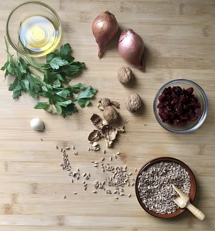 Some of the ingredients needed to make this warm farro salad on a wooden board.