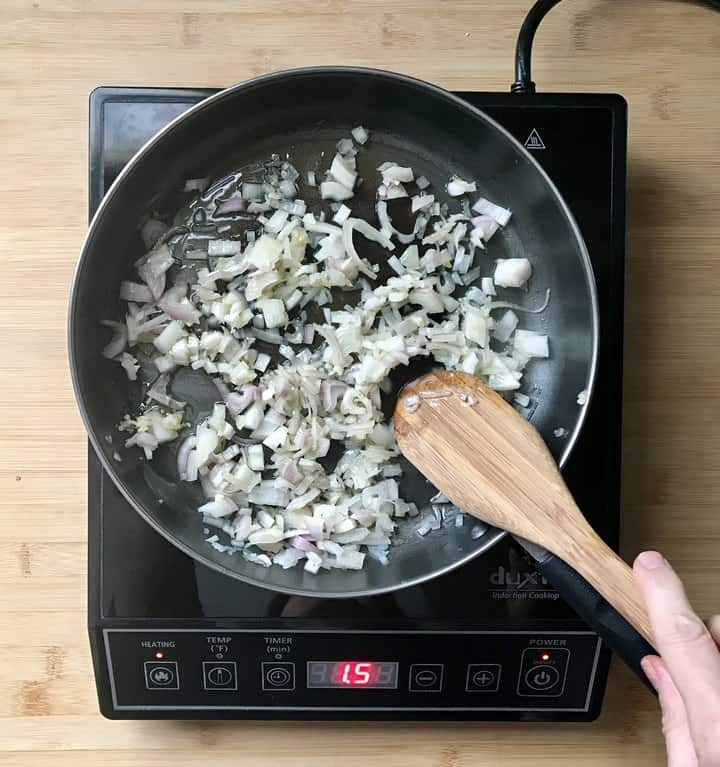 Shallots being sauteed in a pan.