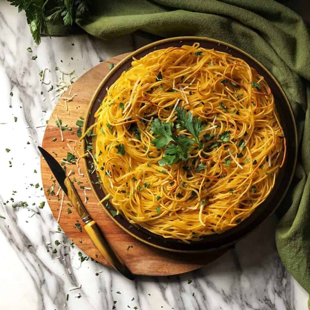 A round platter of spaghetti pie on a wooden board.
