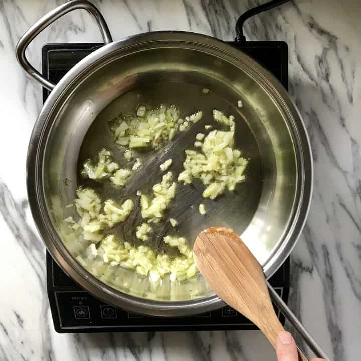 Onions are being sauteed in a saucepan.