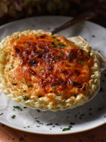 The cheesy topping of a seafood appetizer.